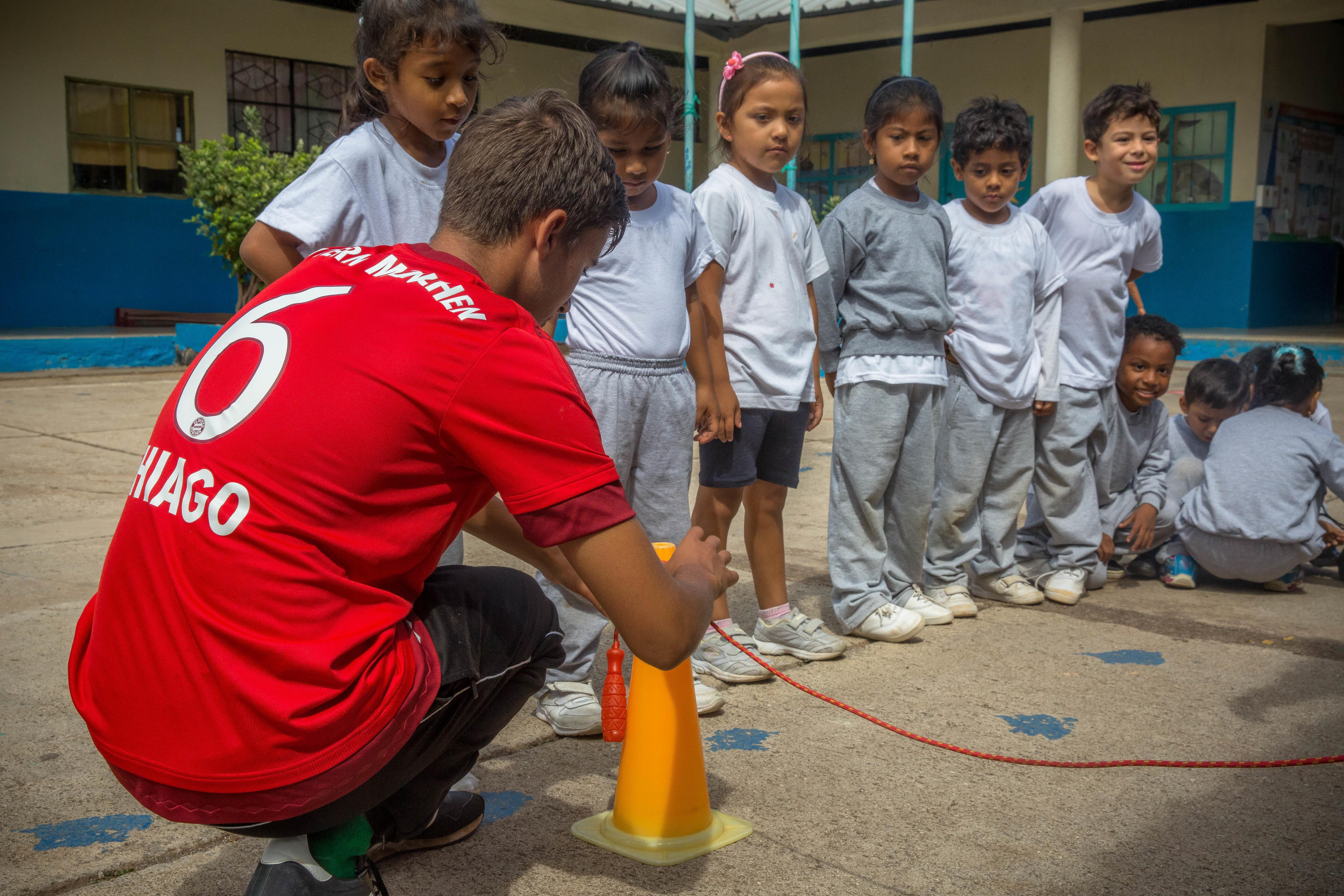 A Projects Abroad volunteer coaching sports in Ecuador helps out with a sports day